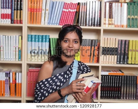 Young Indian Student with books in the library.