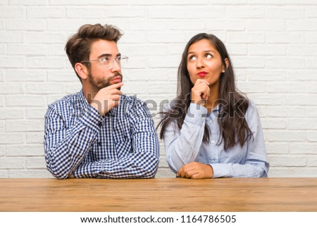 Young indian woman and caucasian man couple doubting and confused, thinking of an idea or worried about something