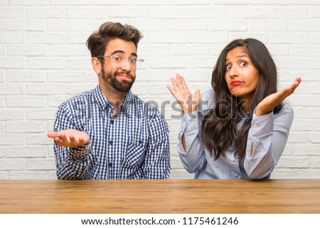 Young indian woman and caucasian man couple doubting and shrugging shoulders, concept of indecision and insecurity, uncertain about something