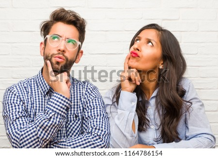 Young indian woman and caucasian man couple thinking and looking up, confused about an idea, would be trying to find a solution