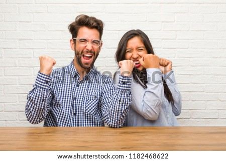 Young indian woman and caucasian man couple very happy and excited, raising arms, celebrating a victory or success, winning the lottery