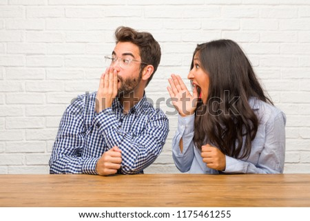 Young indian woman and caucasian man couple whispering gossip undertone, trying not to be heard, is warning of a possible weakness or an opportunity