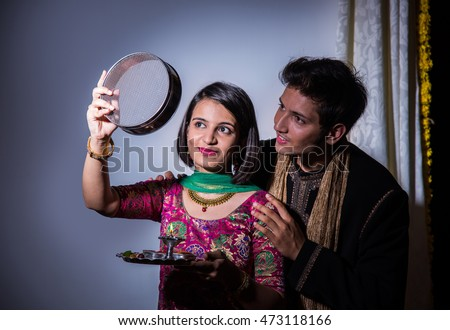 Young Indian woman celebrating Karwa chauth festival with husband