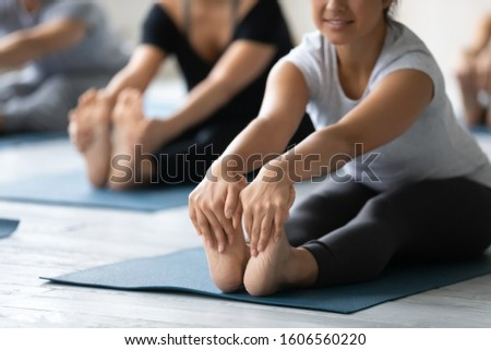 Young Indian woman doing Seated forward bend exercise, feet close up, diverse people practicing yoga at group lesson, stretching in paschimottanasana pose on mat, working out in modern yoga studio