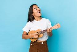 Young indian woman happy playing ukelele isolated