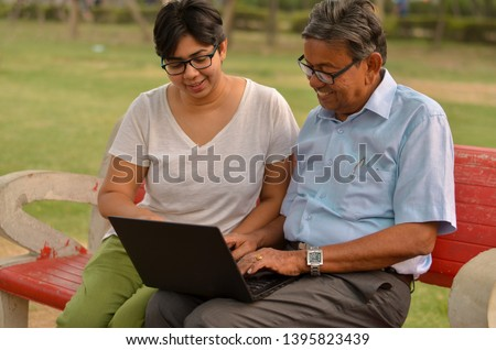 Young Indian woman helping an old Indian man on a laptop sitting on a red bench in a park in New Delhi, India