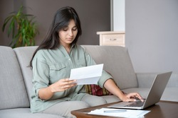 Young indian woman holding letter using laptop computer application paying bill online on website, managing account finances, calculating budget tax banking loan debt payment sitting on couch at home.