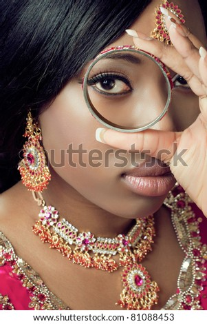 Young indian woman in traditional clothes with golden bridal jewelry, close-up shot