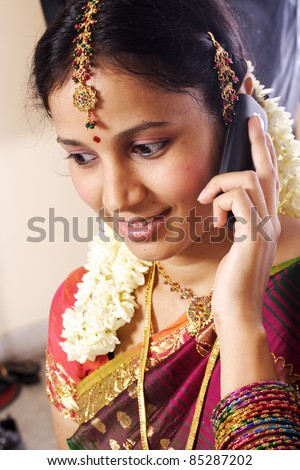 Young Indian woman in traditional clothing talking on cellphone