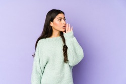 Young indian woman isolated on purple background is saying a secret hot braking news and looking aside