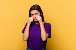 Young Indian woman isolated on yellow background whining and crying disconsolately.