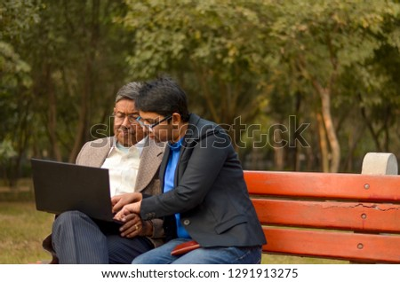 Young Indian woman manager/entrepreneur in western formals or suit helping old Indian man on a laptop promoting digital literacy for elderly in a park in New Delhi, India