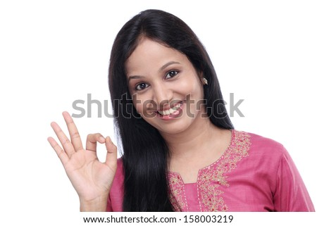 Young Indian woman showing OK sign against white background