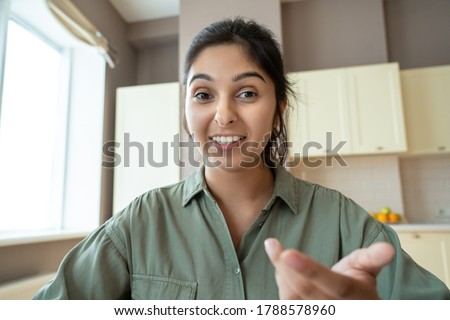 Young indian woman speaking to webcam during conference video call working at home office. Distance teacher or tutor teaching online, giving workshop webinar. Videocall screenshot closeup headshot.