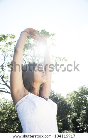 Young indian woman stretching and doing yoga in the park with the sun filtering through her arms.