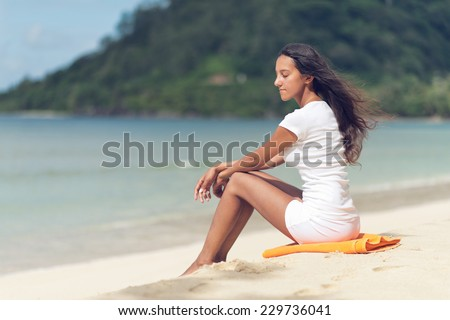 Young Indian Woman Unwinding at the Beautiful Beach with Closed Eyes while Day Dreaming.