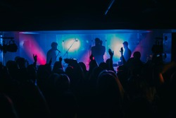 Young indie band performs on stage at the club