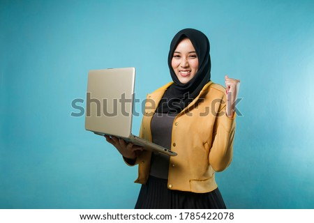 young Indonesian woman holding laptop in victory position on isolated background