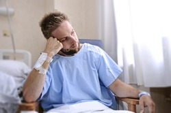 young injured man in hospital room sitting alone in pain looking negative and worried for his bad health condition sitting on chair suffering depression on a sad lonely medical background