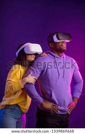 Young interracial couple having first experience of using virtual reality headset, standing joyful and impressed in studio with violet background