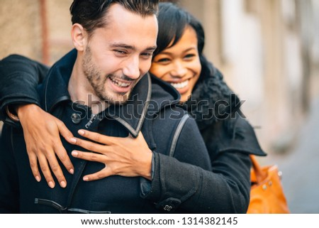Young interracial couple in love having fun on street