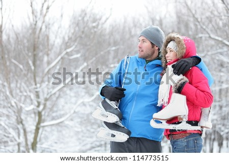 Young interracial couple in winter carrying ice skates standing close together looking out over a snowy winter landscape with copyspace. Asian woman, Caucasian man.