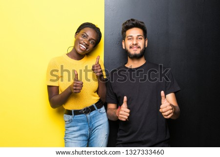 Young interracial couple, indian man and african woman with thumbs up isolated on yellow black background
