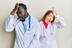 Young interracial couple wearing doctor uniform and stethoscope surprised with hand on head for mistake, remember error. forgot, bad memory concept.