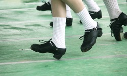 Young Irish Dance Girls Team in a Line on Stage in Hard Jig Shoes