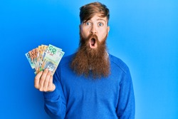 Young irish redhead man holding australian dollars scared and amazed with open mouth for surprise, disbelief face