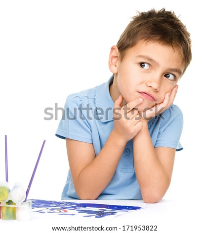 Young is daydreaming while drawing with paints, isolated over white