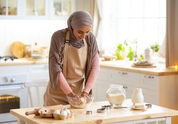 Young Islamic Woman In Hijab Preparing Pastry In Kitchen, Kneading Dough For Cookies While Baking At Home, Positive Muslim Lady In Apron Enjoying Making Homemade Food, Free Space