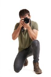 young isolated male photographer kneeling forward photographing, wears green T-shirt, gray jean, and brown boots