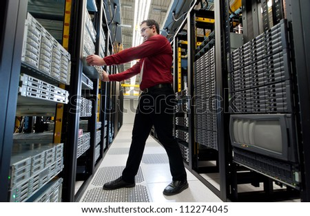 Young IT administrator installing a new rack mount server. Large scale storage server is also seen.