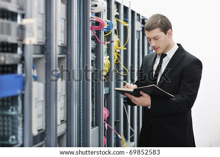 young it engeneer business man with notebook  in network server room