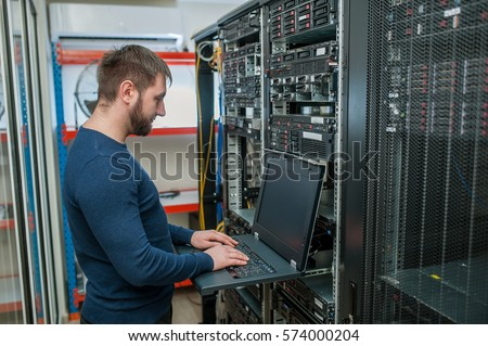 young it engeneer business man with thin modern aluminium laptop in network server room #574000204