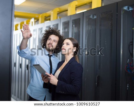 Young IT engineer showing working data center server room to female chief engineer who holding tablet computer #1009610527