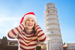 Young, itching from energy and searching for excitement. I'm going to Christmas trip to Italy. It is a no-brainer. Happy woman in Santa hat looking up on something in front of Leaning Tour of Pisa.