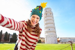 Young, itching from energy and searching for excitement. I'm going to Christmas trip to Italy. It is a no-brainer. Happy woman in Christmas tree hat taking selfie in front of Leaning Tour of Pisa