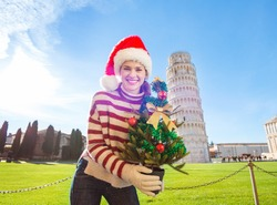 Young, itching from energy and searching for excitement. I'm going to Christmas trip to Italy. It is a no-brainer. Happy woman in Santa hat holding Christmas tree in front of Leaning Tour of Pisa.