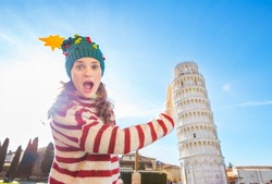 Young, itching from energy and searching for excitement. I'm going to Christmas trip to Italy. It is a no-brainer. Surprised young woman in Christmas tree hat holding Leaning Tour of Pisa