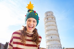 Young, itching from energy and searching for excitement. I'm going to Christmas trip to Italy. It is a no-brainer. Portrait of happy woman in Christmas tree hat in front of Leaning Tour of Pisa