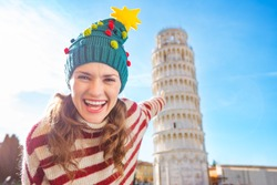 Young, itching from energy and searching for excitement. I'm going to Christmas trip to Italy. It is a no-brainer. Happy woman in Christmas tree hat pointing on Leaning Tour of Pisa
