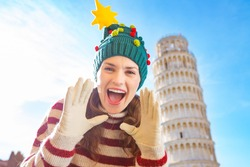 Young, itching from energy and searching for excitement. I'm going to Christmas trip to Italy. It is a no-brainer. Happy woman in Christmas tree hat shouting in front of Leaning Tour of Pisa