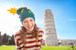 Young, itching from energy and searching for excitement. I'm going to Christmas trip to Italy. It is a no-brainer. Portrait of merry young woman in Christmas tree hat in front of Leaning Tour of Pisa