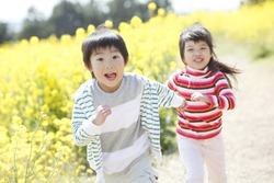 young Japanese boy and Japanese girl running in a field