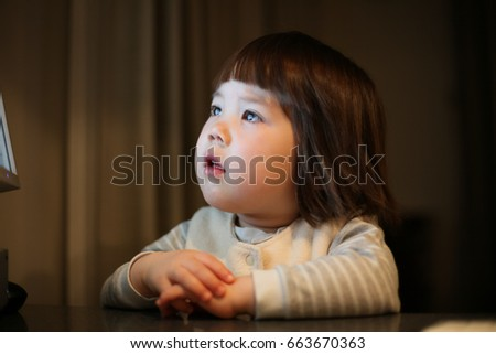 Young Japanese girl fascinated by a computer screen. #663670363