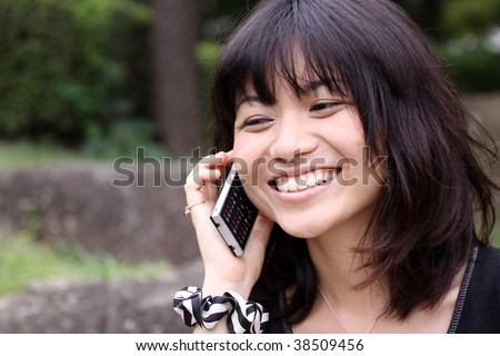 Young Japanese girl laughing while talking on the phone