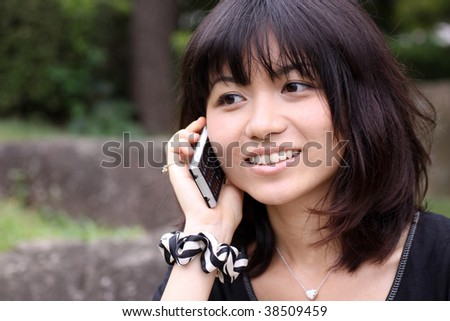 Young Japanese girl worried while talking on the phone