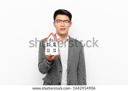 young japanese man feeling puzzled and confused, with a dumb, stunned expression looking at something unexpected with a house model